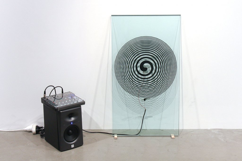 "<p class=""p1"">Joyce Hinterding, <em>Glass Spiral Network – V001, </em>2011, graphite, glass, speaker, sound deck, glass panel, 90 x 50 cm</p>"